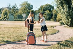 有背包的吃冰淇凌的两个女小学生女朋友背面图  免版税库存图片
