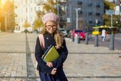 有背包的困厄的女孩孩子,笔记本,在外套和法国贝雷帽 免版税库存图片