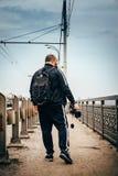 有背包的在手中走在城市桥梁,从后面,透视的看法的男性摄影师旅客和照相机,被定调子 免版税库存照片