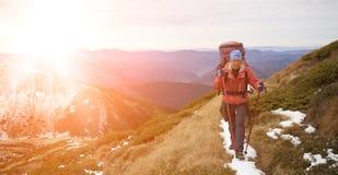 有背包的女孩在一座高山的上面上升 库存照片