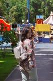 有背包的女孩在夏天走在公园 免版税库存图片