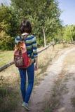 有背包的女孩在森林旅行 免版税库存图片