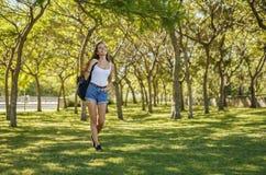 有背包的女孩走在公园的 免版税库存图片