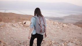 有背包的妇女在沙漠走 慢的行动 女孩在干燥沙子和岩石漫步 惊人的山风景 股票录像