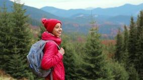 有背包的妇女徒步旅行者,佩带在红色夹克和橙色裤子,站立在山和森林背景 股票视频