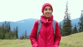 有背包的妇女徒步旅行者,佩带在红色夹克和橙色裤子,走在山背景 股票视频