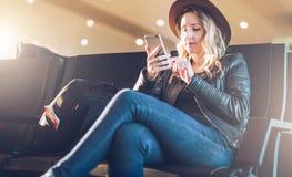 有背包的妇女游人在机场坐,使用智能手机 行家女孩等待平面着陆,检查电子邮件 免版税图库摄影