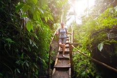有背包的妇女游人沿着走竹台阶在密林  库存照片