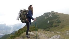 有背包的妇女走在到达上面的石倾斜的山的 股票录像