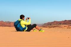 有背包的妇女远足者在沙漠做照片 库存图片