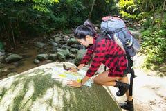 有背包的妇女远足者在自然保护区检查地图在瀑布和森林发现方向 免版税库存图片