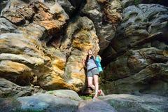 有背包的妇女远足者探索美丽的五颜六色的峡谷和做照片的在智能手机 免版税图库摄影