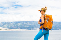 有背包的妇女远足者,远足在海边和山 免版税库存图片