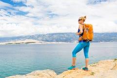 有背包的妇女远足者,远足在海边和山 免版税库存照片