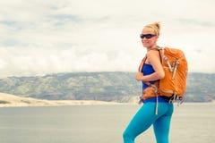 有背包的妇女远足者,远足在海边和山 库存图片