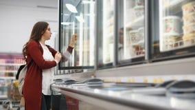 有背包的妇女从冰箱选择产品在超级市场 股票视频