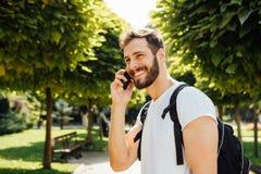 有背包的学生谈话在手机 免版税图库摄影
