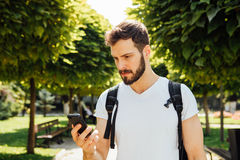 有背包的学生谈话在手机 免版税库存图片
