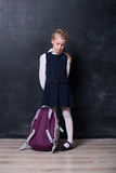 有背包的小女小学生在黑板附近 免版税库存图片