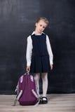 有背包的小女小学生在黑板附近 免版税库存照片