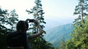 有背包的少妇游人拍在小山和山的智能手机美好的全景的照片 影视素材