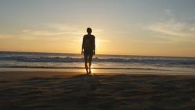 有背包的少妇游人走在海滩的到海洋在日落和被举的手 去在含沙的女孩远足者 股票视频