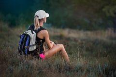 有背包的少妇游人,基于一个草甸, e的 免版税库存照片