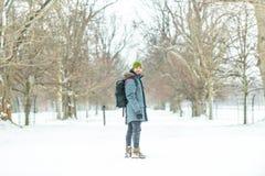 有背包的年轻人在雪 免版税图库摄影