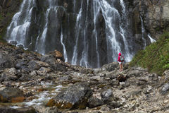 有背包的年轻俏丽的旅游女孩在瀑布附近 库存照片