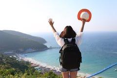 有背包的年轻女人旅客享用和站立在海背景的山,酸值Larn在芭达亚市,春武里市的 免版税库存照片
