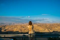 有背包的年轻女人站立在山顶部 免版税图库摄影