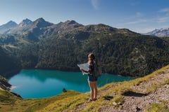 有背包的年轻女人读一张地图的在瑞士阿尔卑斯 作为背景的湖ritom 库存照片