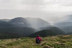 有背包的年轻女性远足者在草坐在小山顶部 库存图片