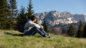 有背包的年轻旅客人站立在山顶部,享受惊人的看法 游人拍与智能手机的照片 股票录像