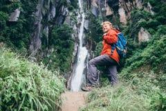 有背包的年轻旅游人在多雨moun的瀑布附近 库存图片