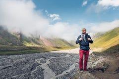 有背包的年轻男性旅客沿山河的谷走以山和云彩为背景 免版税图库摄影