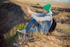 有背包的年轻远足者坐山上面,当休息在活跃步行以后时 远足在美好的自然在晴天, 免版税库存图片