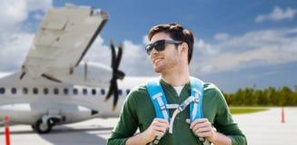 有背包的微笑的人在机场的飞机 免版税库存照片