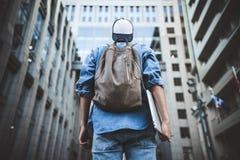 有背包的快乐的年轻人享受步行的有膝上型计算机和短冷期的城市 库存照片