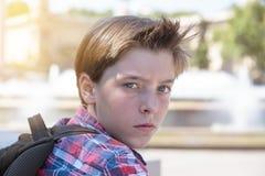 有背包的恼怒的十几岁的男孩 库存照片