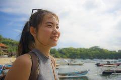 有背包的愉快的亚裔中国妇女在暑假和假期旅行的海滩旅行旅游游览微笑的甜点 免版税库存照片