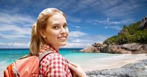 有背包的愉快的妇女在塞舌尔群岛海滩 库存照片