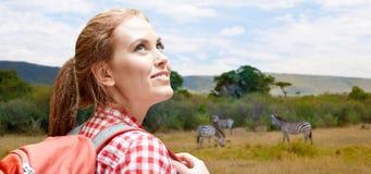 有背包的愉快的妇女在非洲大草原 免版税库存图片