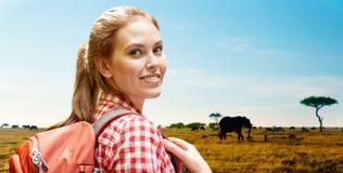 有背包的愉快的妇女在非洲大草原 库存图片