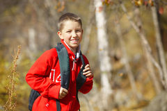 有背包的愉快的微笑的远足者男孩 库存图片