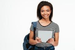 有背包的愉快的微笑的非洲少年女孩使用个人计算机片剂 免版税库存图片