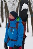 有背包的愉快的挡雪板在森林里站立 库存图片