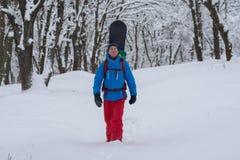有背包的愉快的挡雪板通过森林走 免版税库存图片