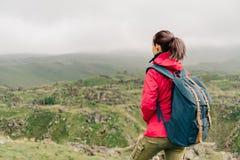 有背包的探险家女孩走在山的 库存照片