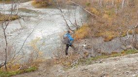 有背包的旅客是在足迹 他在特别棍子通行证帮助下接近山小河和 股票视频